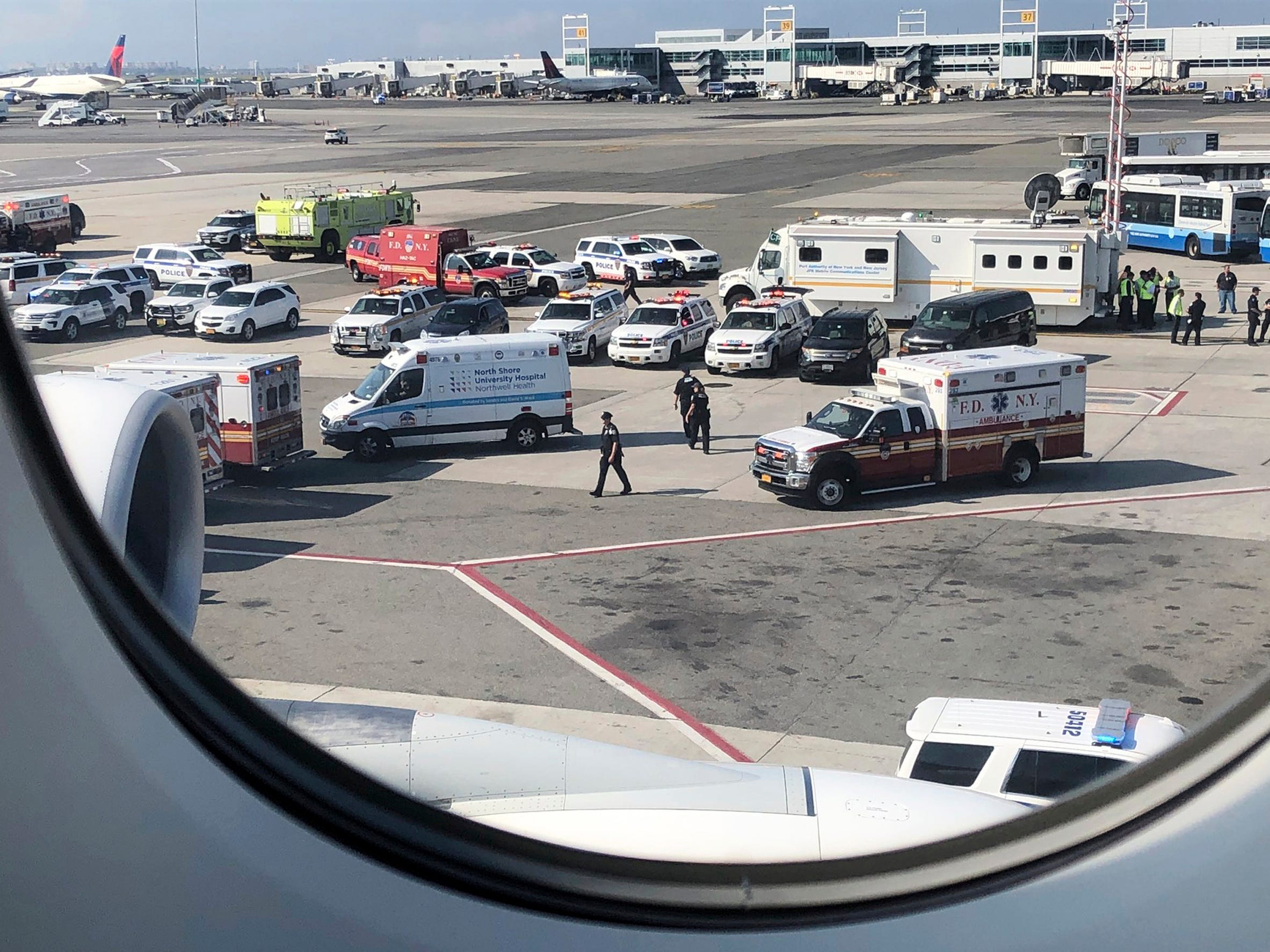 Emergency response crews gather outside a plane at New York's Kennedy Airport amid reports of ill passengers aboard a flight from Dubai, Sept. 5, 2018.