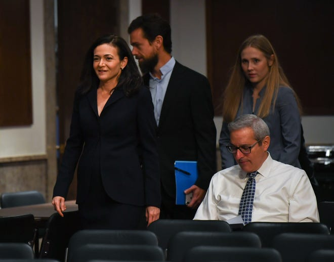 Sheryl Sandberg, chief operating officer of Facebook Inc., left, and Jack Dorsey, chief executive officer of Twitter Inc., center, arrive to a near empty room to testify before the Senate Select Committee on Intelligence on Sept. 5, 2018 in Washington.