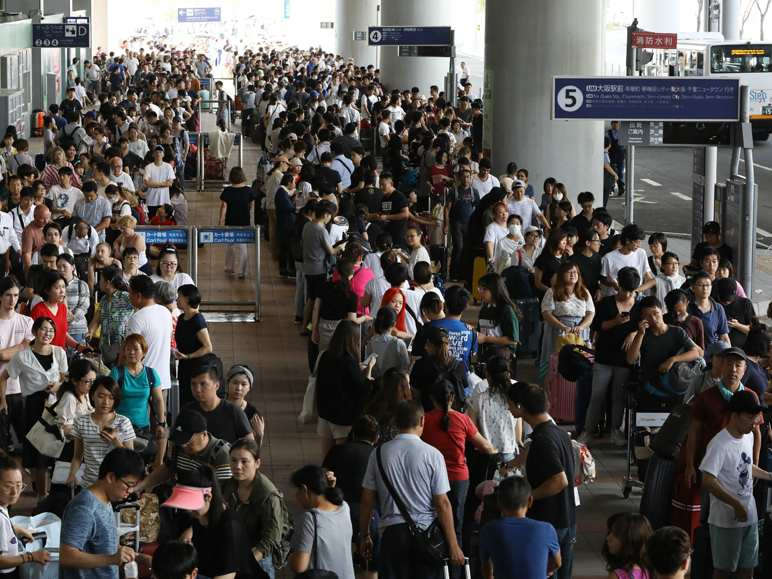 Passengers stranded overnight at the Kansai International Airport due to typhoon Jebi queue for buses that will transport them from the airport in Izumisano city, Osaka prefecture on Sept. 5, 2018. The major airport was cut off when a huge typhoon smashed through its sole access road and was being evacuated on Sept. 5, as Japan grappled with devastation caused by its most powerful storm in a quarter of a century.