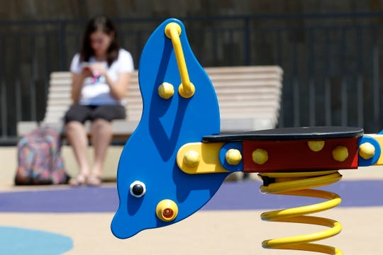 A girl uses her cell phone in a playground in southern France.