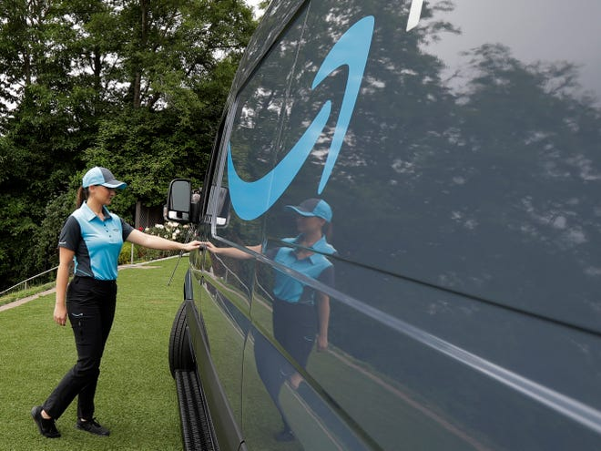 "FILE- In this June 27, 2018, file photo, Parisa Sadrzadeh, a senior manager of logistics for Amazon.com, opens the door of an Amazon-branded delivery van at the request of a photographer in Seattle, following a media event for Amazon to announce a new program that lets entrepreneurs around the country launch businesses that deliver Amazon packages. Amazon says it has ordered 20,000 vans for its new delivery program. The online retailer says ""tens of thousands"" of individuals have applied for the program, and it had to up its van order to 20,000 from 4,500. (AP Photo/Ted S. Warren, File)"