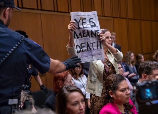A protester disrupts the proceedings as President Donald Trump's Supreme Court nominee, Brett Kavanaugh, appears before the Senate Judiciary Committee for the second day of his confirmation hearing on Capitol Hill in Washington on Sept. 5, 2018.