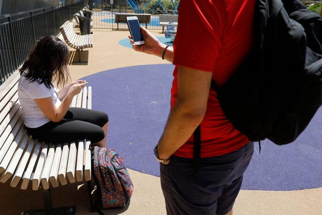 Young people use their mobile phones in Nice, southern France. The French government has banned mobile phones and related devices in schools.