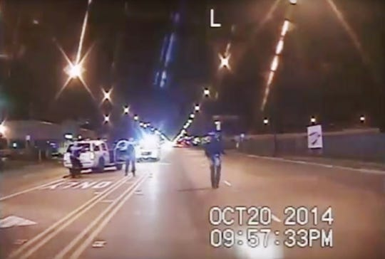 In this Oct. 20, 2014, image from dash-cam video provided by the Chicago Police Department, Laquan McDonald, right, walks down the street moments before being shot by police officer Jason Van Dyke in Chicago.