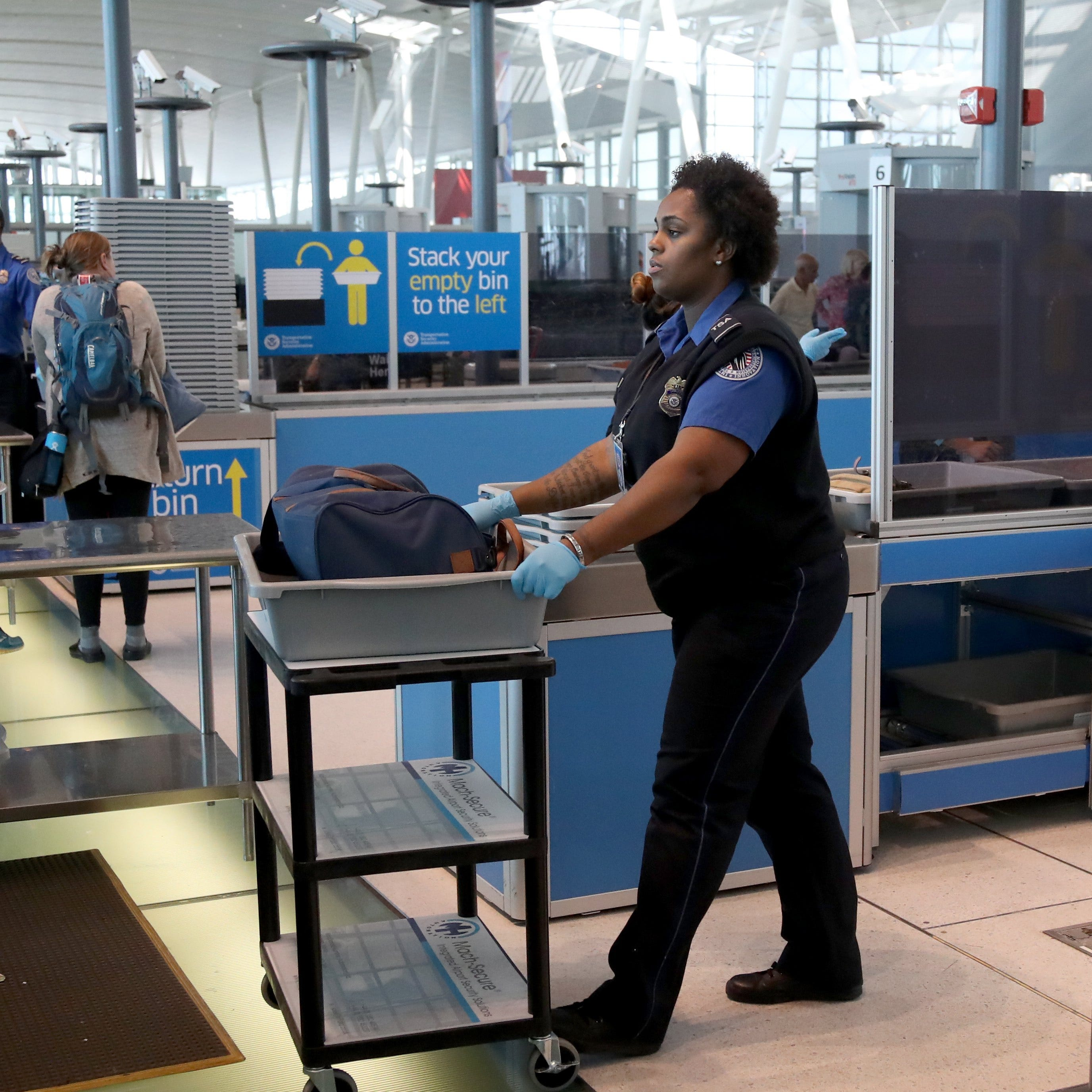 An employee of the Transportation Security Administration (TSA) handles a bag inside a plastic tray for secondary screening at a checkpoint at John F. Kennedy International Airport (JFK) in Queens, New York.