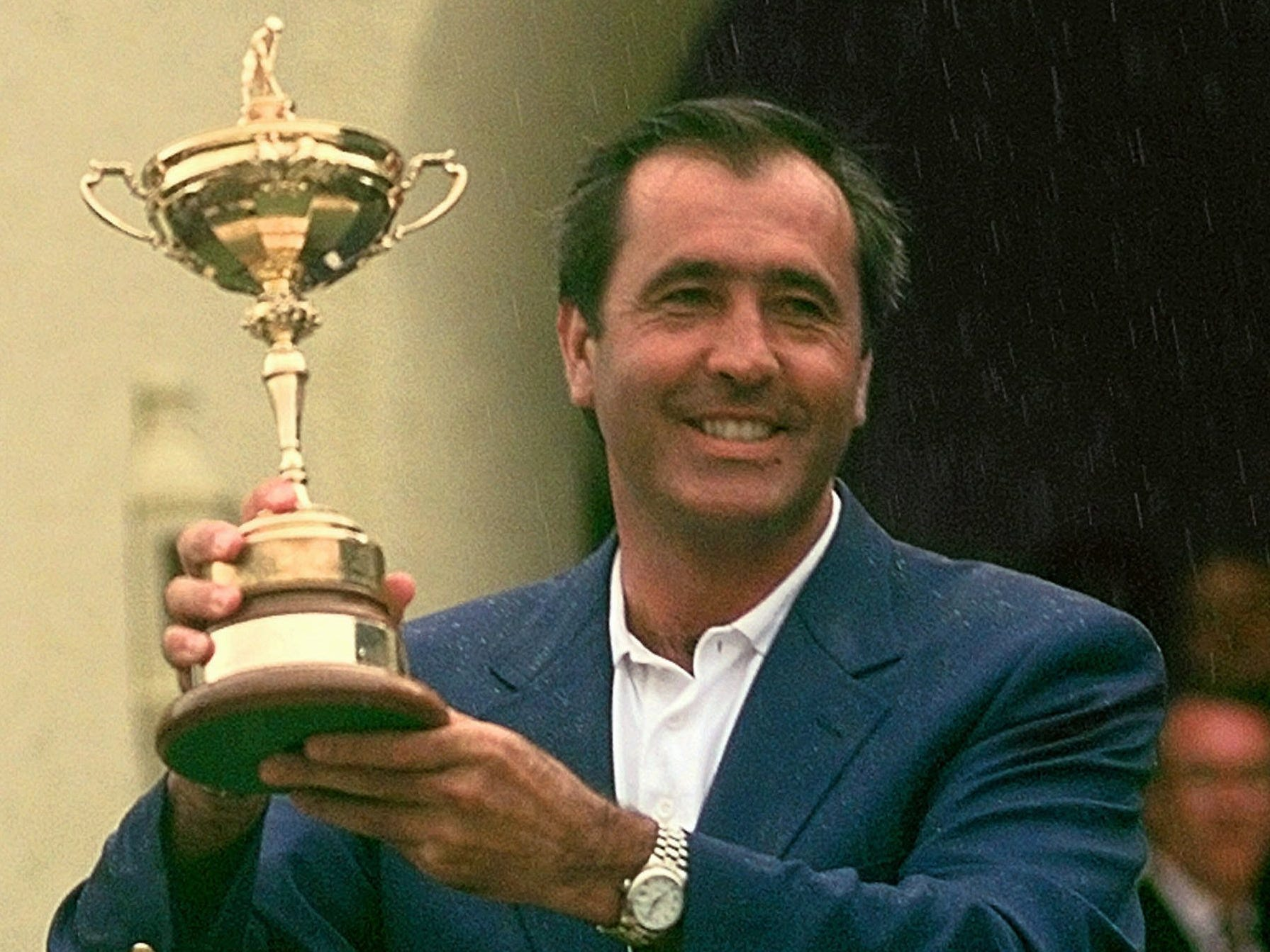 Team Europe, 1997: European Ryder Cup team captain Seve Ballesteros holds the trophy in the rain after Europe beat the United States 14.5-13.5.