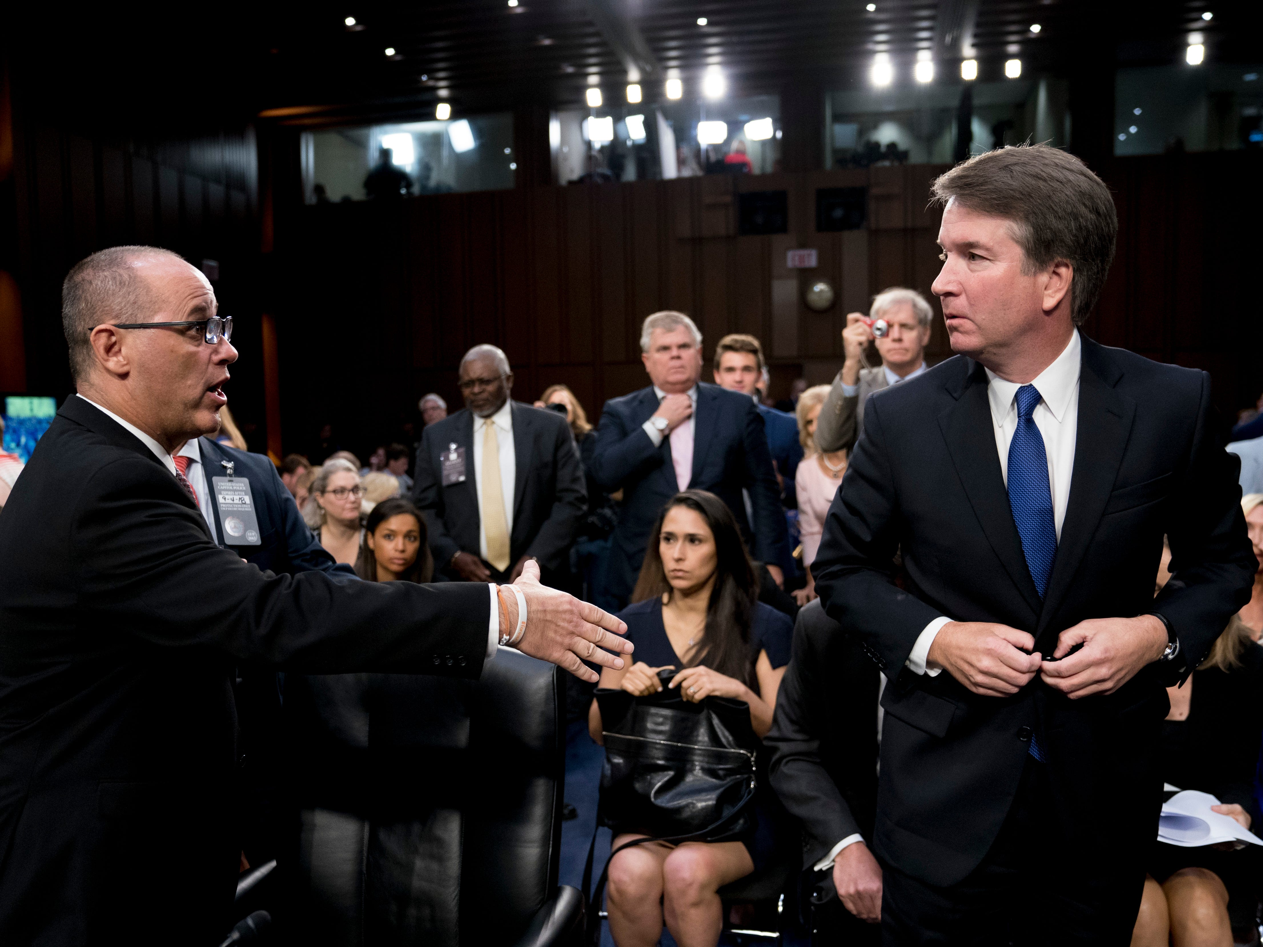 Fred Guttenberg, the father of Jamie Guttenberg who was killed in the Stoneman Douglas High School shooting in Parkland, Fla., left, attempts to shake hands with President Donald Trump's Supreme Court nominee, Brett Kavanaugh, right, as he leaves for a lunch break while appearing before the Senate Judiciary Committee on Capitol Hill in Washington, Tuesday, Sept. 4, 2018, to begin his confirmation to replace retired Justice Anthony Kennedy. Kavanaugh did not shake his hand. (AP Photo/Andrew Harnik) ORG XMIT: DCAH244