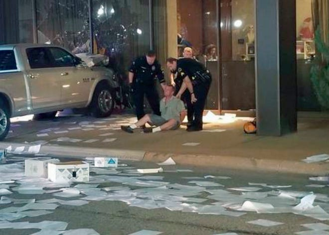In this image taken from video by KDFW Fox 4 a man is detained after crashing his pickup into the side of the Fox affiliate television station building in downtown Dallas on Sept. 5, 2018.