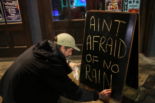 Nick Eberlein, bartender at The Merry Widow, draws a new sign as Tropical Storm Gordon arrives Sept. 4, 2018, in Mobile, Ala.