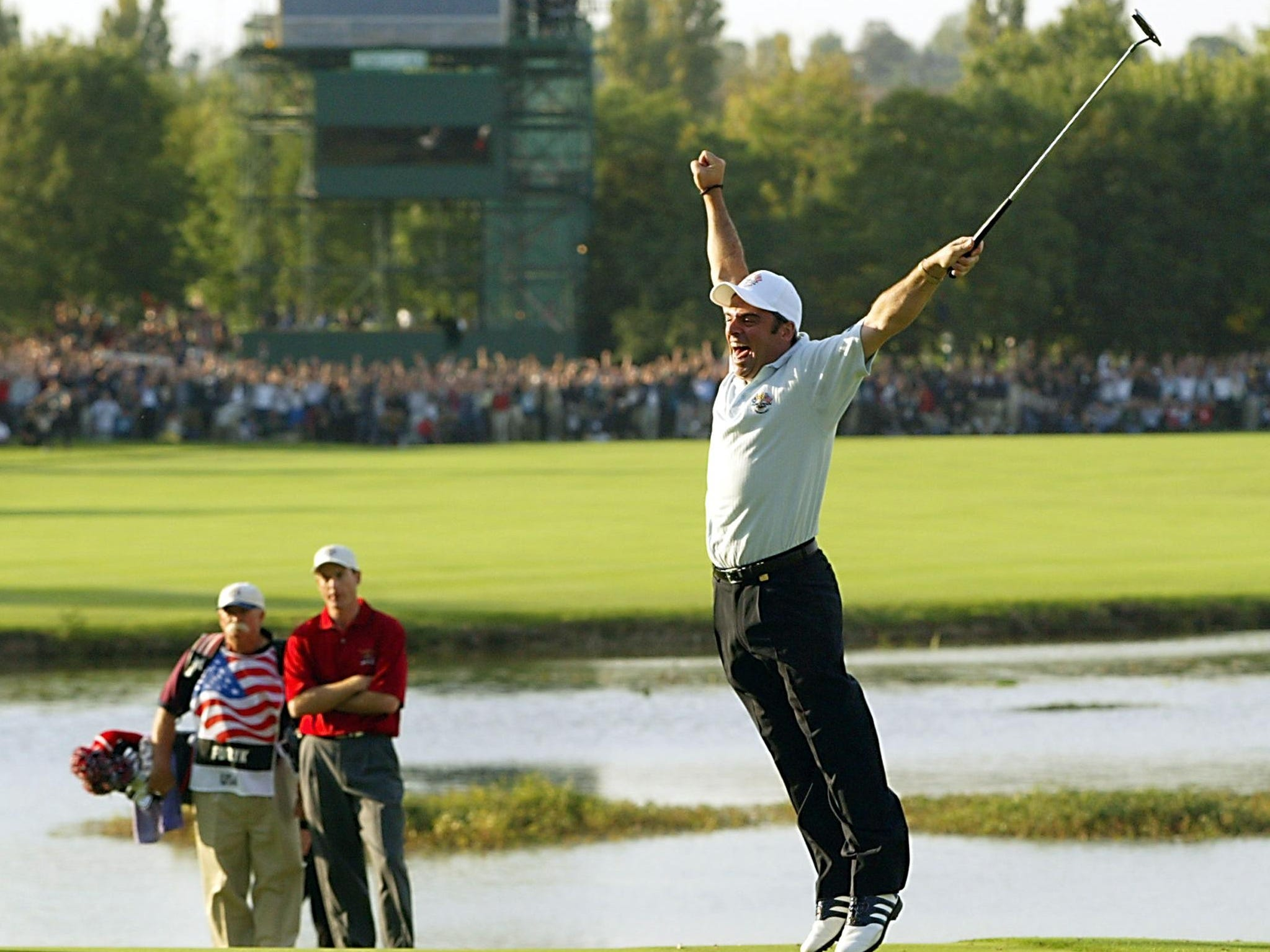 Team Europe, 2002: Paul McGinley leaps in the air after sinking the winning putt on the 18th green to win the Ryder Cup as Team USA's Jim Furyk and his caddie Mike Cowen look on. Europe won 15.5-12.5