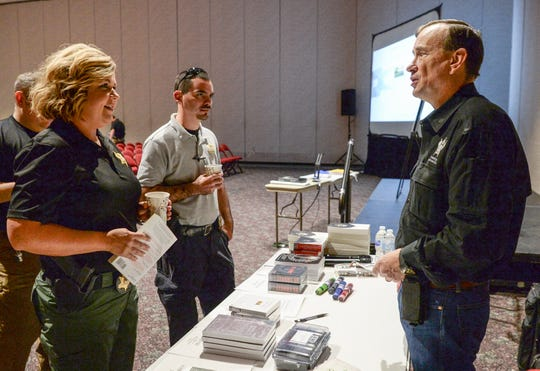 Oconee County Sheriff's Office Deputy Trace Burch, left, talks with Dave Grossman, director of the Illinois-based Killology Research Group, before a school-safety seminar at the Civic Center of Anderson on Thursday.