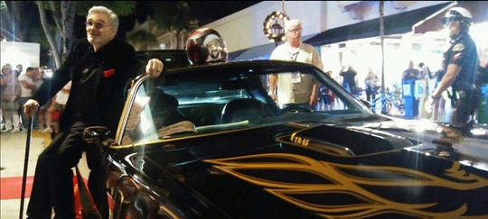"""Burt Reynolds poses with the Pontiac Trans Am that served as the inspiration for using  the sports car in """"Smokey and the Bandit."""" The iconic car is owned by Anderson resident Rena Martino."""