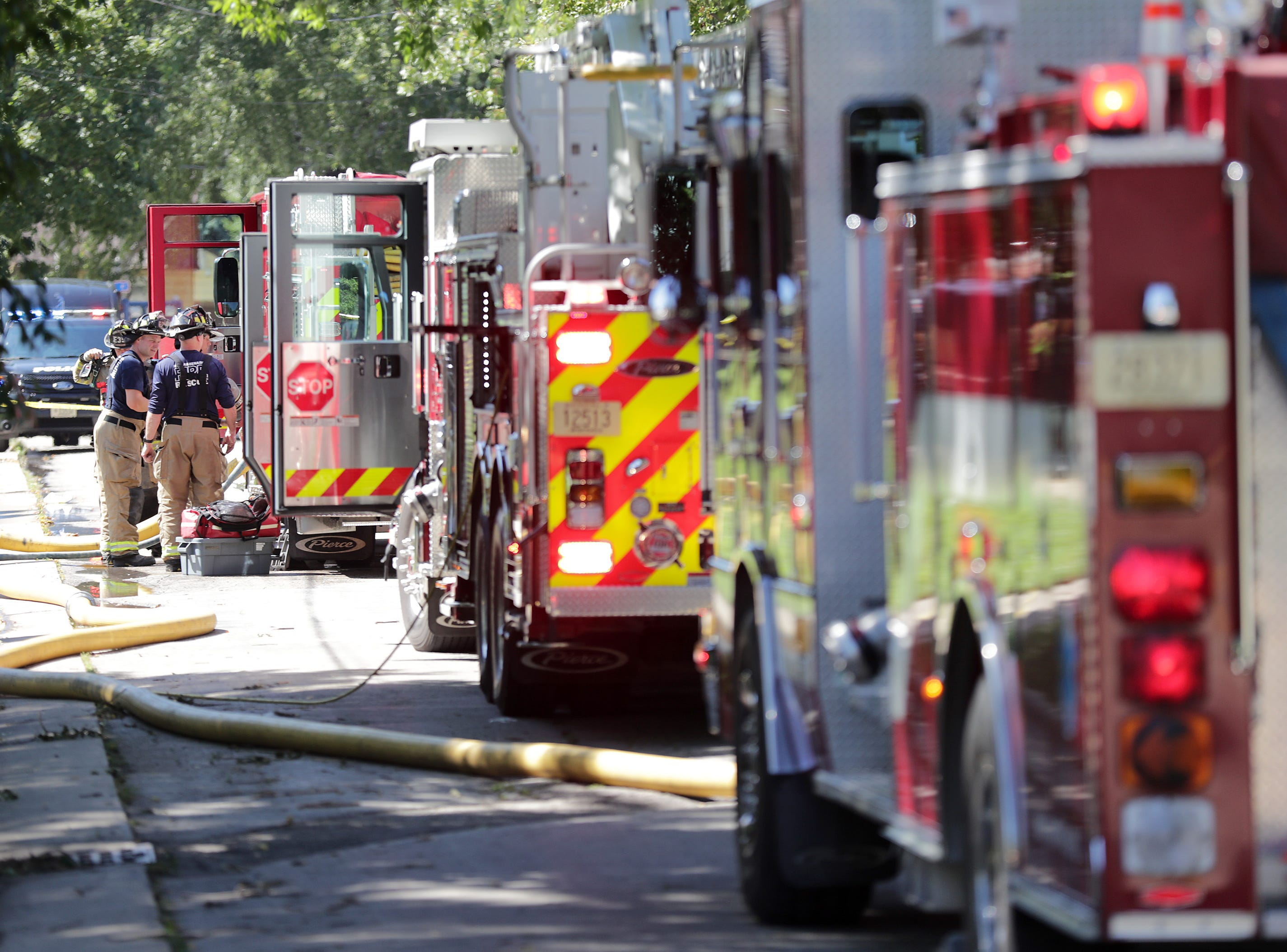 Firefighters and police on the scene of a structure fire in the 100 block of First Street,   on Thursday, September 6, 2018, in Menasha, Wis.  Kevin Kloehn, chief of Neenah-Menasha Fire Rescue, said one person was injured and three others were rescued in the fire.