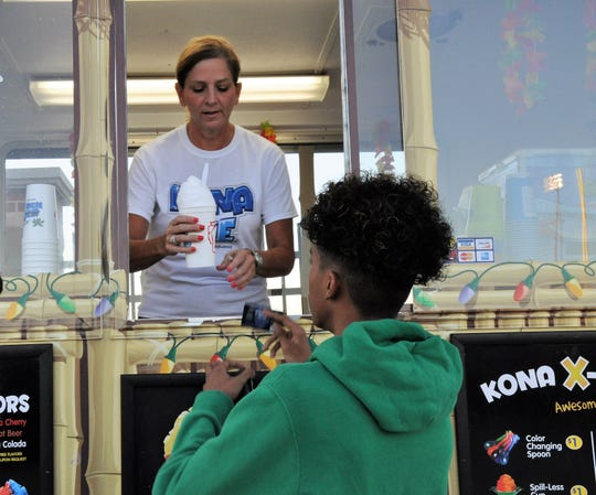 Barbara McLeod, owner of the Kona Ice truck, hands an order to a customer during the Cooper football game at Shotwell Stadium on Aug. 31.