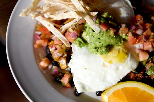 The huevos rancheros at Famous Toastery is two eggs served over black beans, topped with cheddar and feta cheese, served with with crispy tortilla strips. The dish is then topped with cilantro, pico de gallo and avocado slices.