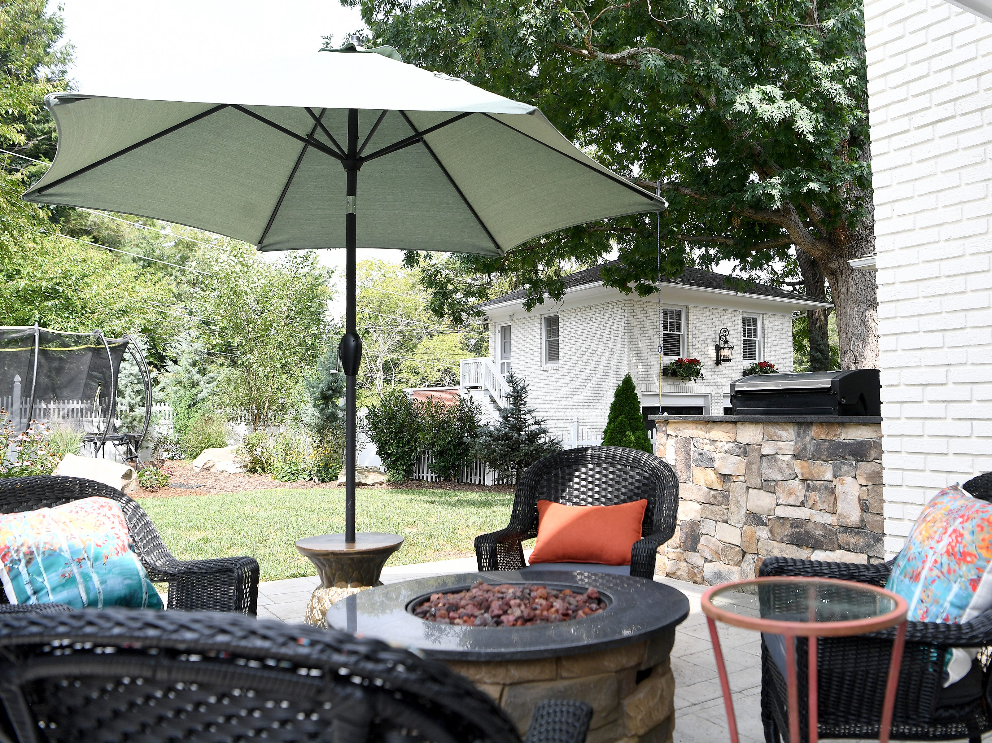 The backyard of the Bryant family's historic North Asheville home features plenty of room for entertaining with a fire table and grill. Also shown is the carriage house, or detached garage, which matches the main home architecturally.
