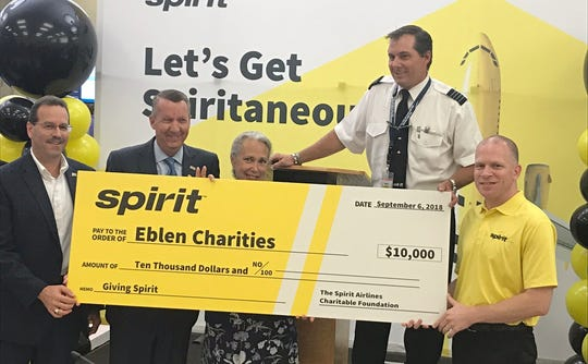 Asheville resident and Spirit Airlines pilot John Podlewski, second from right, poses with a $10,000 check to Eblen Charities on Thursday in a ceremony at the Asheville Regional Airport.