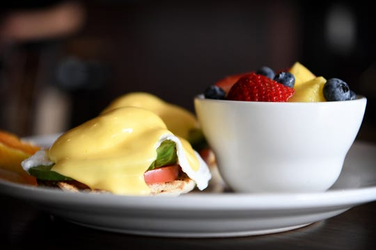 The Cali Benedict at Famous Toastery is poached eggs, avocado and tomato on an English muffin covered with house-made Hollandaise. Shown here with a side of fresh fruit.