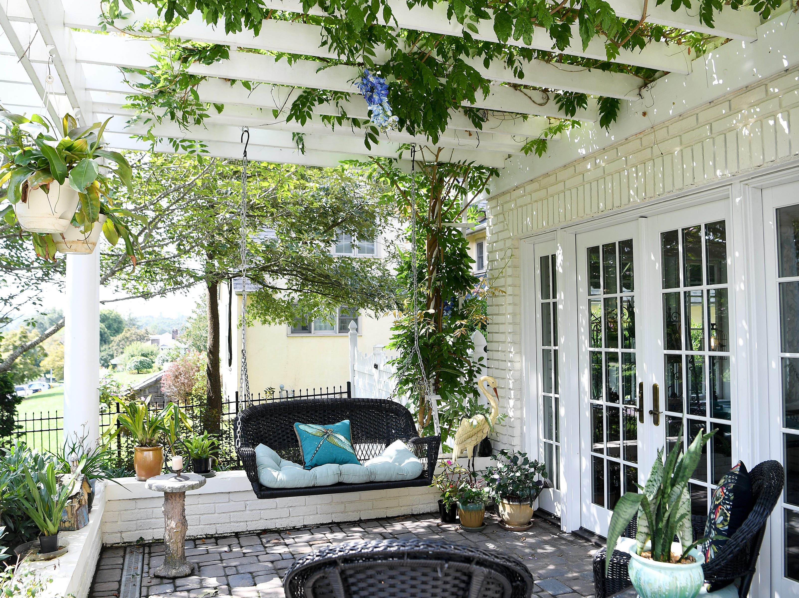 The front porch of the Bryant family's home in North Asheville features seating and wisteria-covered roofing which gives a pop of purple when in bloom.