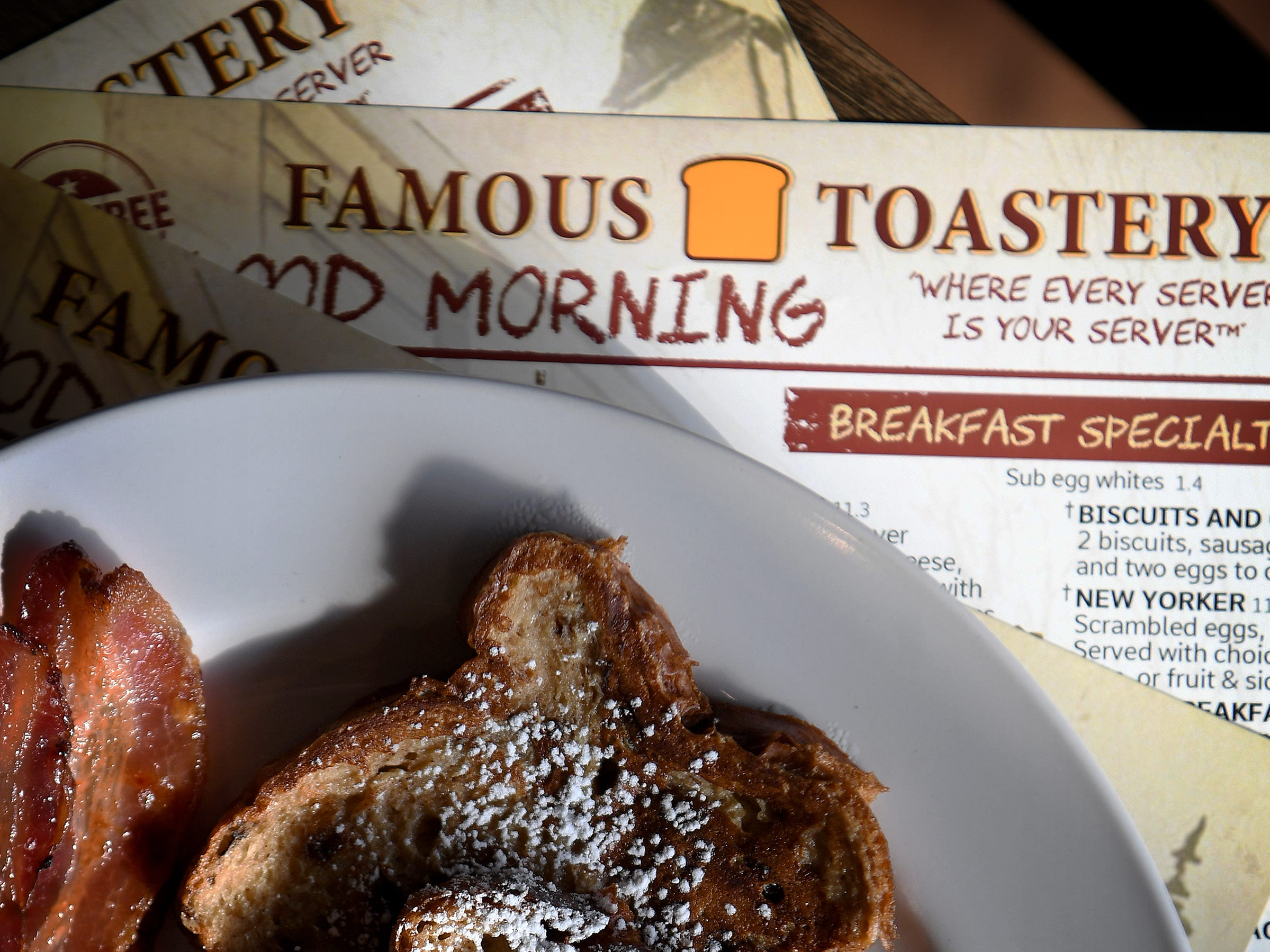 The cinnamon raisin French toast at Famous Toastery, here served with bacon, is a breakfast favorite.