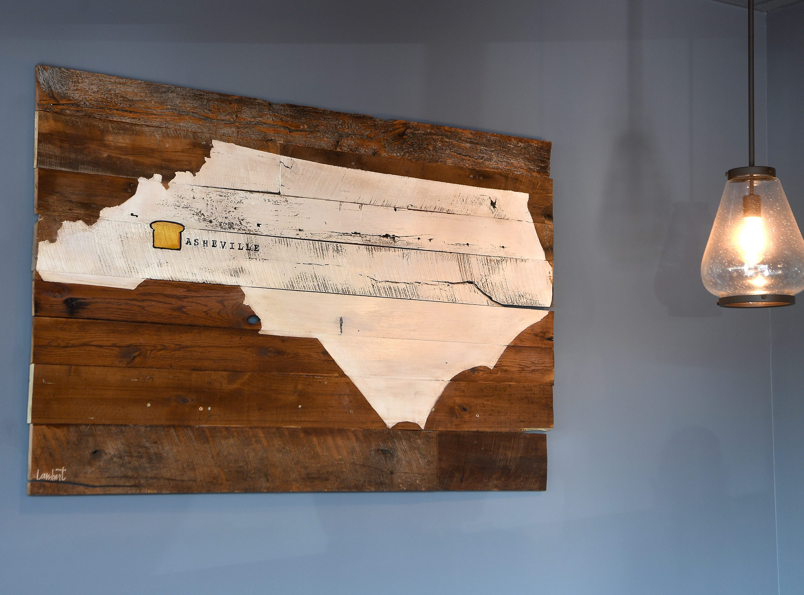 Custom Asheville touches hang on the walls of Famous Toastery, a franchise started in Huntersville, North Carolina which recently opened an Asheville location.