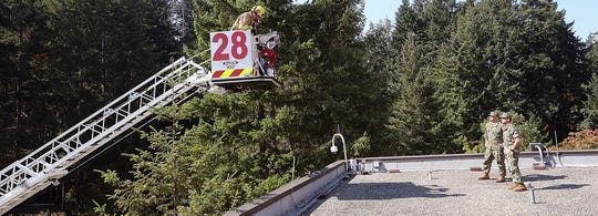 """Navy Region Northwest Ladder 28 moves into position to """"rescue"""" Tyler Castellanos and Chad Galvin from atop one of the roofs of Naval Hospital Bremerton during an earthquake drill on Thursday."""