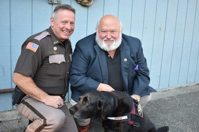 Mason County Sheriff Casey Salisbury and Belfair resident Kevin Swett with Swett's facility dog, Maxine. Swett volunteers with Maxine multiple times a month at the Mason County Jail to provide comfort to inmates.