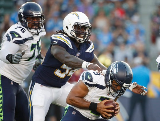 Seattle Seahawks quarterback Russell Wilson, right, is sacked by Los Angeles Chargers defensive end Melvin Ingram during a preseason football game  Aug. 18