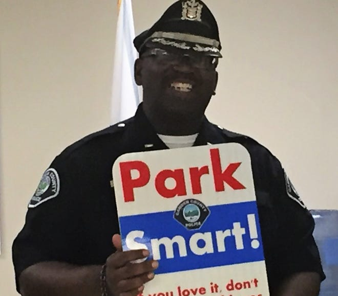Camden County Police Lt. Zsakhiem James shows a Park Smart sign at a press conference Thursday.