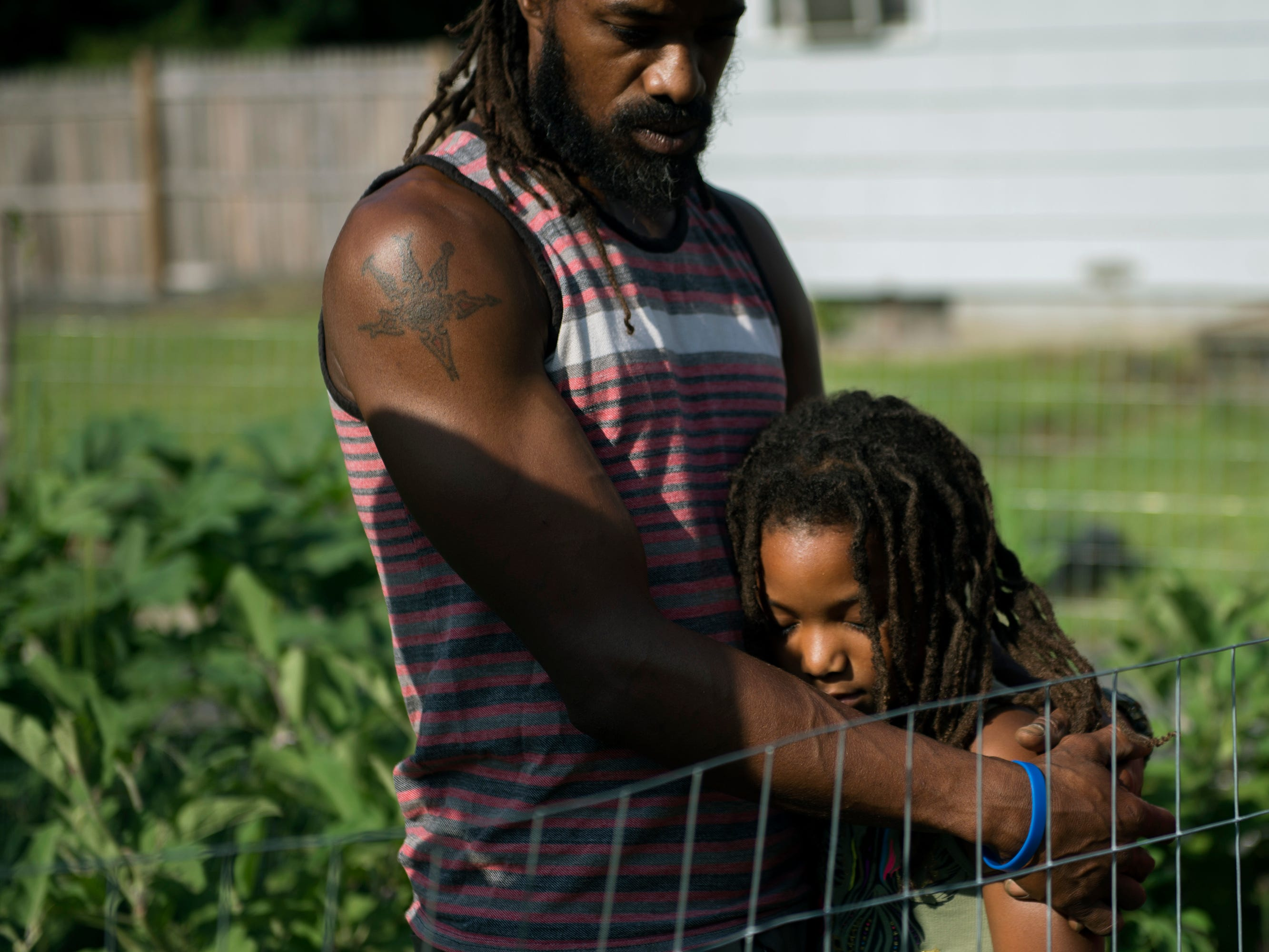 Micaiah Hall embraces his daughter Araminta, 7, on their family farm Thursday, Aug. 23, 2018 at Free Haven Farms in Lawnside, N.J.