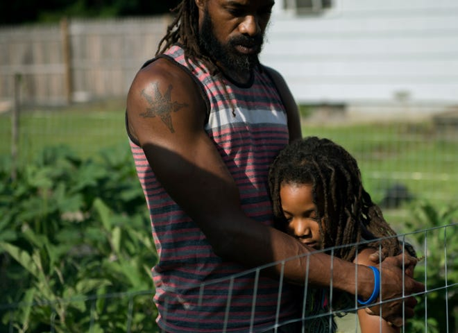 Micaiah Hall embraces his daughter Araminta, 7, on their family farm at Free Haven Farms in Lawnside.
