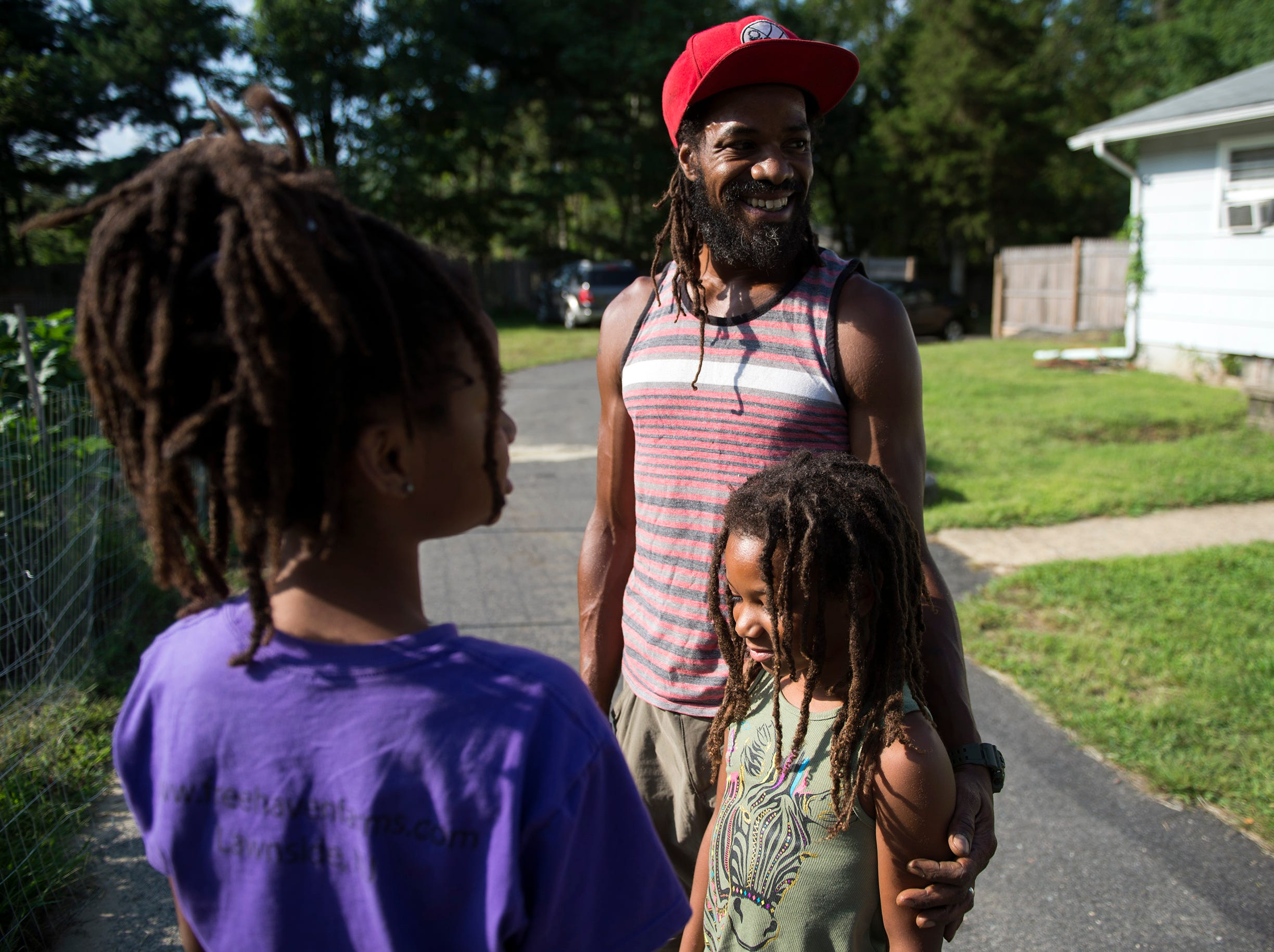 Farmer Micaiah Hall smiles alongside his daughters Araminta, 7, right, and Adia, 10, at their farm Thursday, Aug. 23, 2018 in Lawnside, N.J.