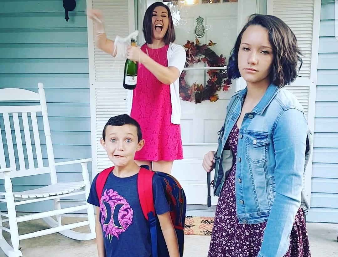 Someone's having fun with that first-day-of-school photo: Mom celebrates as seventh-grader Carli and second-grader Lucas return to school in Upper Deerfield.