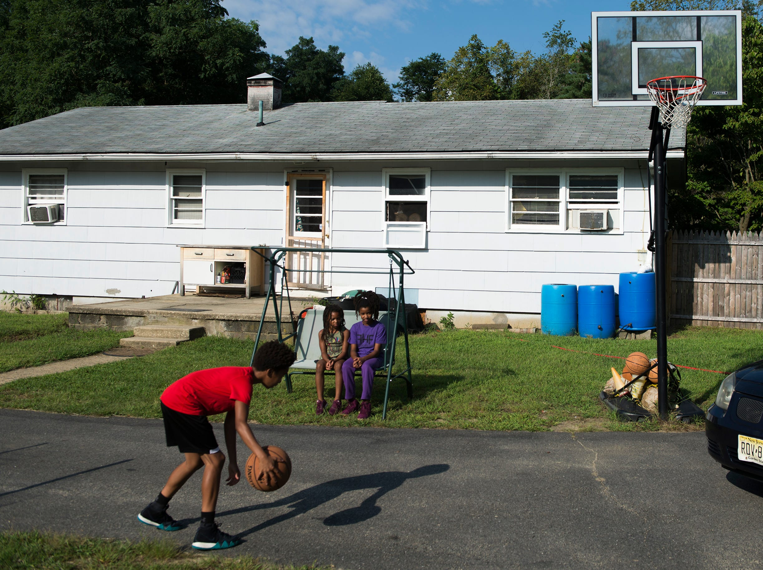 Satifa Hall, 12, plays basketball in the driveway of his home Thursday, Aug. 23, 2018 in Lawnside, N.J.