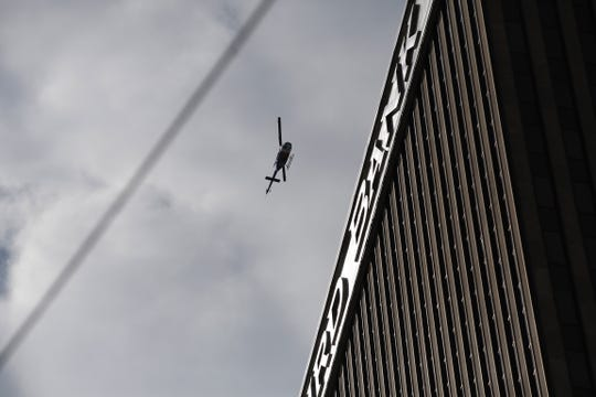 A helicopter flies over Fifth Third Center downtown.