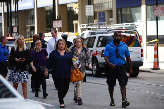Police escort people away from the area where an active shooter was reported at the Fifth Third Center in Downtown Cincinnati.