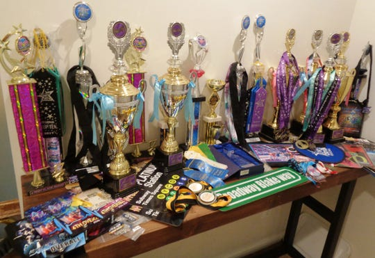 "Medals and trophies earned by the dancing of ""Broadway"" Blake cover a table in the Funk family home in Loveland."