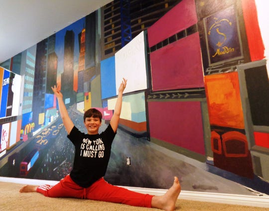 """""""Broadway"""" Blake strikes a dance pose in front of the New York City mural on the wall of his bedroom in Loveland."""