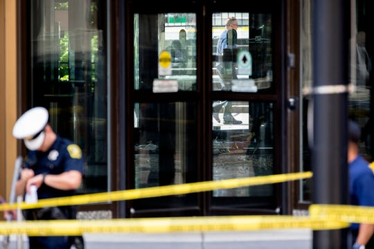 "Shattered glass and police tape are visible at the Fifth Third Bank Center at Fountain Square Thursday, September 6, 2018. Four people are dead including the shooter and several injured after an ""active shooter"" situation in Downtown Cincinnati at the Fountain Square Fifth Third location."