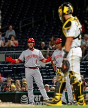 Cincinnati Reds' Eugenio Suarez (7) gestures to Pittsburgh Pirates catcher Francisco Cervelli, right, as he stands on first base after being hit by a pitch from Pirates starting pitcher Jameson Taillon during the fifth inning of a baseball game in Pittsburgh, Wednesday, Sept. 5, 2018.