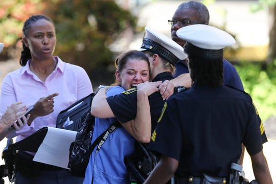 A woman is comforted by authorities stationed outside the University of Cincinnati Medical Center's Emergency room following a mass shooting in downtown Cincinnati that left four dead and several injured, Thursday, Sept. 6, 2018, in Cincinnati. (Kareem Elgazzar, The Cincinnati Enquirer)