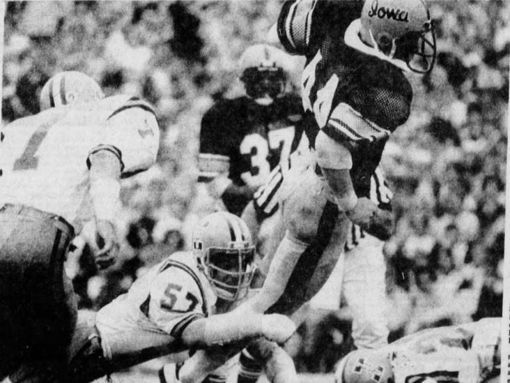 Iowa's Jon Lazar (44) lunges out of the grasp of Iowa State's Mark Settle (57) to score a touchdown in the 1977 Cy-Hawk football game.