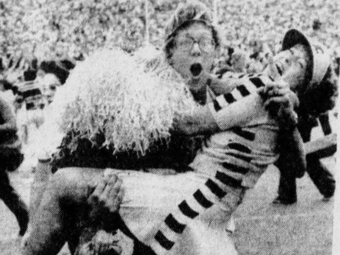 Hans Boehm of Ogden jubilantly lofts pompon girl Janet Long after Iowa's 12-10 win against Iowa State in the 1977 Cy-Hawk football game in Iowa City.