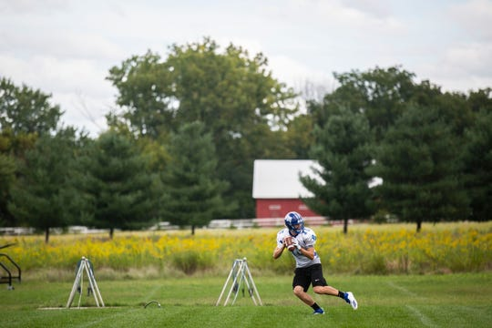 Starting Van Meter quarterback, Anthony Potthoff, passes a football to a coach during practice on Tuesday, Sept. 4, 2018, at the team's practice field in Van Meter.