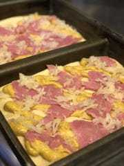 Mustard pizza is topped with bits of corned beef and sauerkraut.