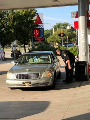 Officer Todd Bing helps pump gas for Dolores Marotta on Aug. 30.
