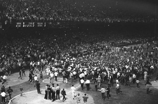 Police in the foreground are helpless as fans pour from the stands in front of the Detroit Tigers dugout after the Tigers beat the New York Yankees to win the American League pennant. Scoreboard shows the final score in Detroit on Sept. 17, 1968. (AP Photo)