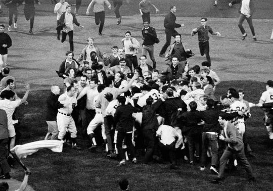 Fans run onto the field at Tiger Stadium to surround the Detroit Tigers after Don Wert's ninth-inning single scored the winning run against the New York Yankees on Sept. 17, 1968.  The victory clinched the American League pennant for the Tigers.