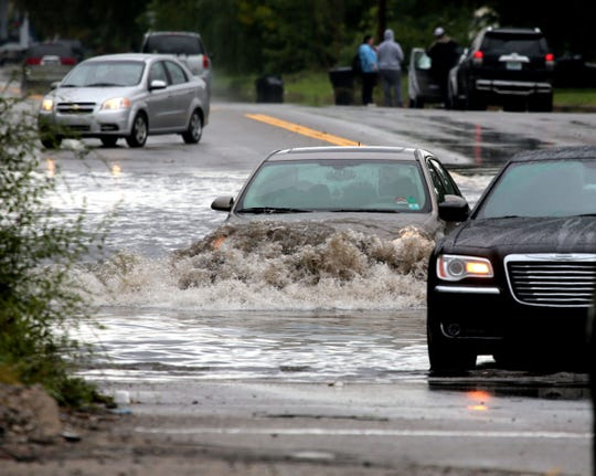 Motorists travel through a flooded section of Oakland St. in Highland Park in September  2016 after heavy rains flooded sections of the Detroit area.