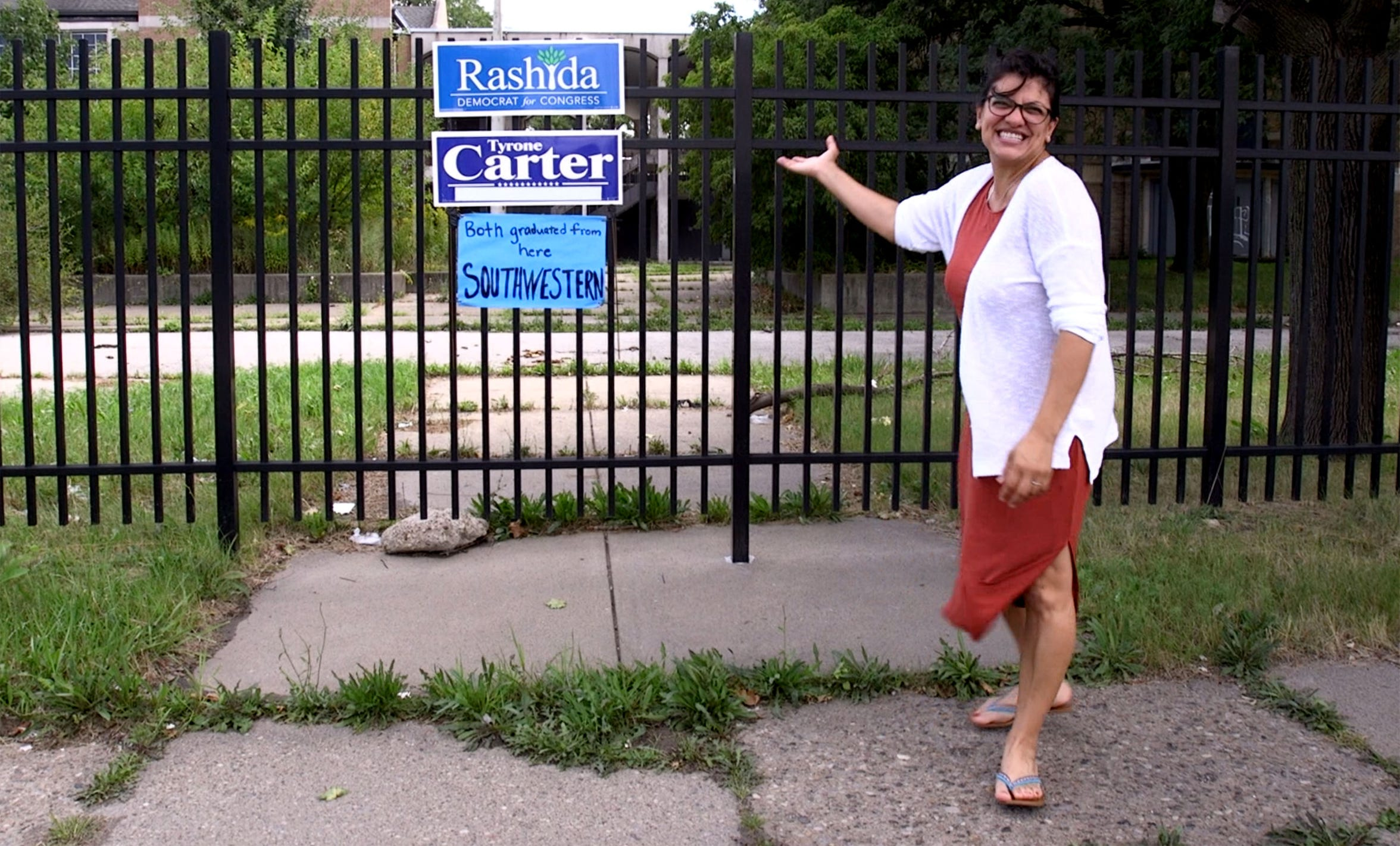 Rashida Tlaib proudly shows off a sign someone made and hung on a gate at a now closed Southwestern High School where Tlaib attended on August 21, 2018 in Detroit.